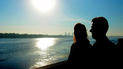 silhouette of couple near wide river against sunrise