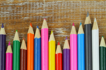 Colorful pencils on rustic wooden surface with copy space