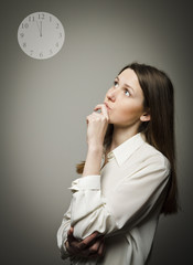 Thinking. Young woman and clock.