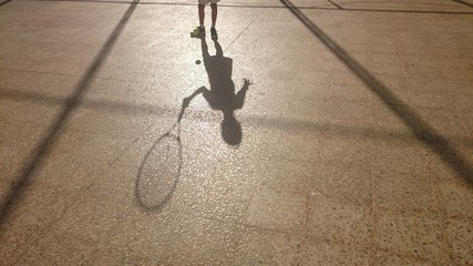Sombra de niño con raqueta y pelota