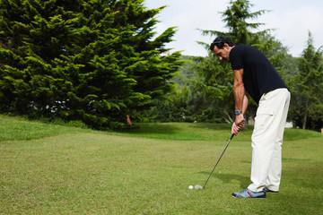 Golfer man hitting golf ball standing on beautiful course