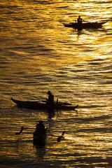 Silhouette photo. Fishermen catch fish at sunset. Beautiful suns