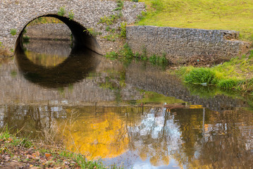 Reflection of the stone bridge in the water.