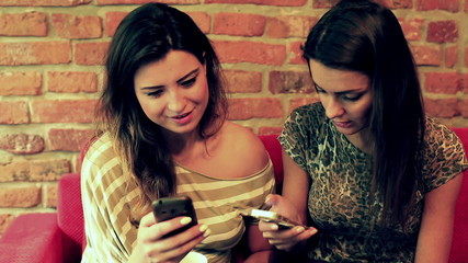 Happy women sitting on the sofa and using smartphones