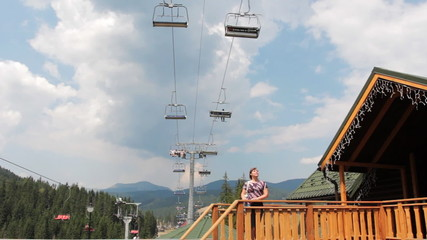 woman looks onto mountain lift in Carpathians, panorama to sky