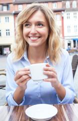 Frau mit blonden Locken liebt frischen Kaffee