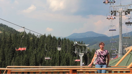 woman sits on handrail fence under mountain lift in Carpathians