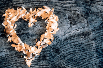 A heart from petals lying on a wooden table