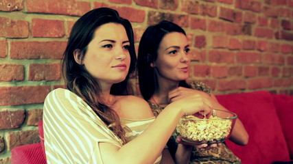Women eating popcorn and watching comedy on television
