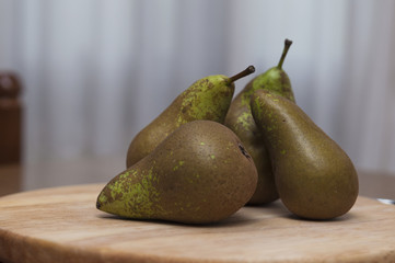 Green pears on wooden table background