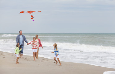 Family Parents Girl Children Flying Kite on Beach