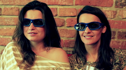Women watching movie in 3d glasses and sitting on the sofa