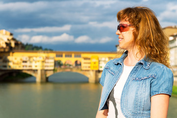 Young female tourist in front of the Ponte Vecchio, Florence