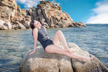 A beautiful freediver girl kissed by the sun on a rock