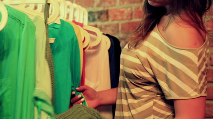 Woman looking on green blouse in the boutique