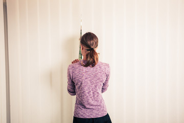 Young woman standing by the blinds
