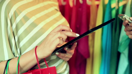Women holding shopping bags and using modern technology