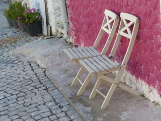 Gartenstühle vor einem rosa Haus in Alacati in der Türkei