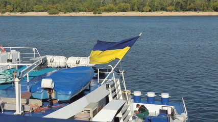 worker tries to find cause of accident ship, above flag Ukraine