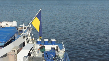 worker repairing equipment on deck of ship, at top flag Ukraine