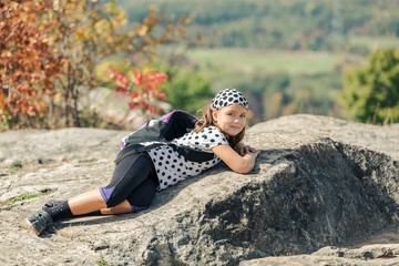tired little happy girl lying and relaxing on stone cliffs