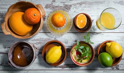 Zitrusfrüchte, Jiaogulan und frischer Saft auf einem Holztisch