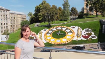 pretty woman has rest in center near real flower clock
