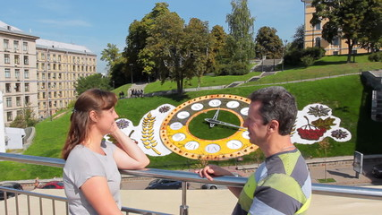 couple looking at each other and chat in Kiev near flower clock