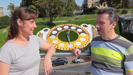 woman with man chat and join hands in Kiev near flower clock