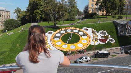 pretty woman has rest in Kiev near real flower clock, back view