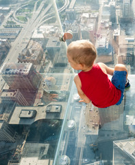 Boy looking down at city from skyscarper