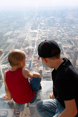 Boys looking down at city from skyscarper