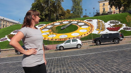 pretty woman stands and looks at real flower clock in Kiev