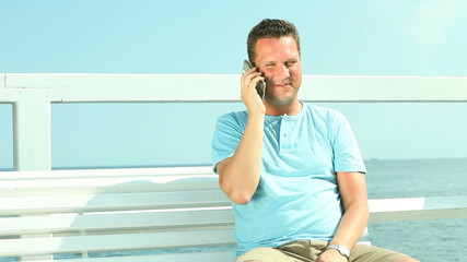 Happy man talking with smartphone by sea