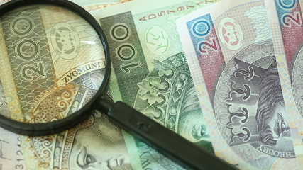Polish zloty banknotes with magnifying glass