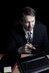 Businessman showing anger over data on computer