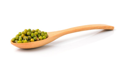 Raw mung beans in wooden spoon over white background