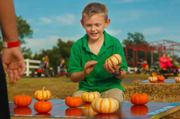 Boy concentrating on finishing pumpkin tic tac toe game outside