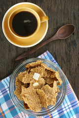 Breakfast cereal with a black coffee on a wooden board