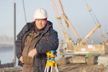 Инженер на стройке делает измерения