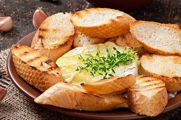 Baked Camembert cheese with thyme and toast rubbed with garlic