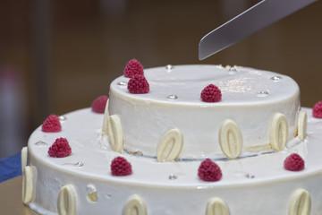 cutting a raspberry cake
