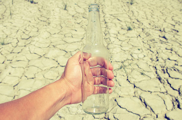 Empty glass bottle from under the water in a hand