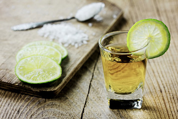 Tequila shot with lime and salt on vintage wooden background