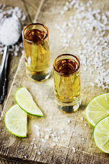 Tequila with lime and salt on vintage wooden background