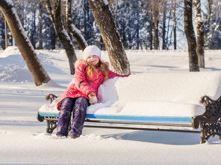 little girl sitting on a bench full of snow
