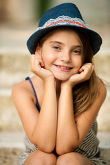 Cute young girl with hat sitting on stairs in park