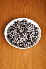 heap of frozen black currant in a plate on the wooden surface