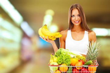 Shopping concept. Beautiful young woman with fruits and