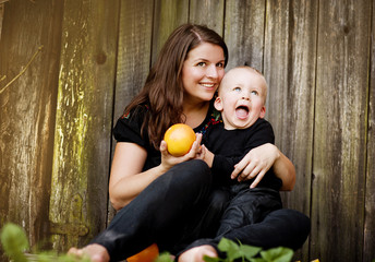 Mother and son eating orange
